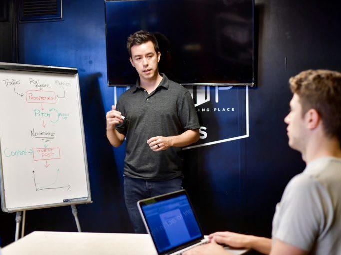 Ein Mann steht vor einen Flipchart. Das Flipchart ist beschriftet. Ein weiterer Mann schreibt an seinem Laptop.