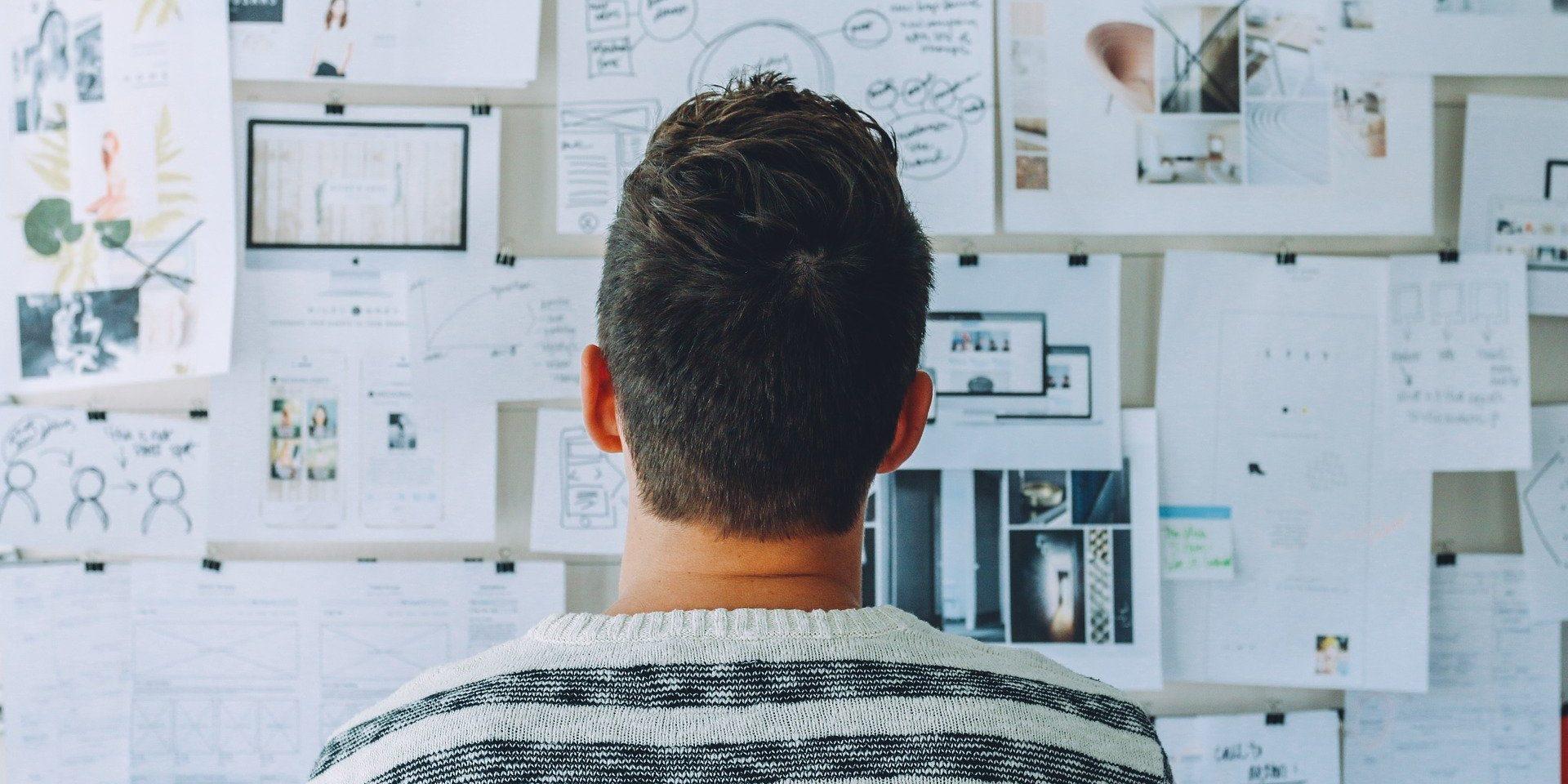 Auf dem Foto sieht man ein jungen Mann, der auf eine Pinnwand mit Notizen blickt. Die Notizen beinhalten Texte über Anforderungen an ein Unternehmen.