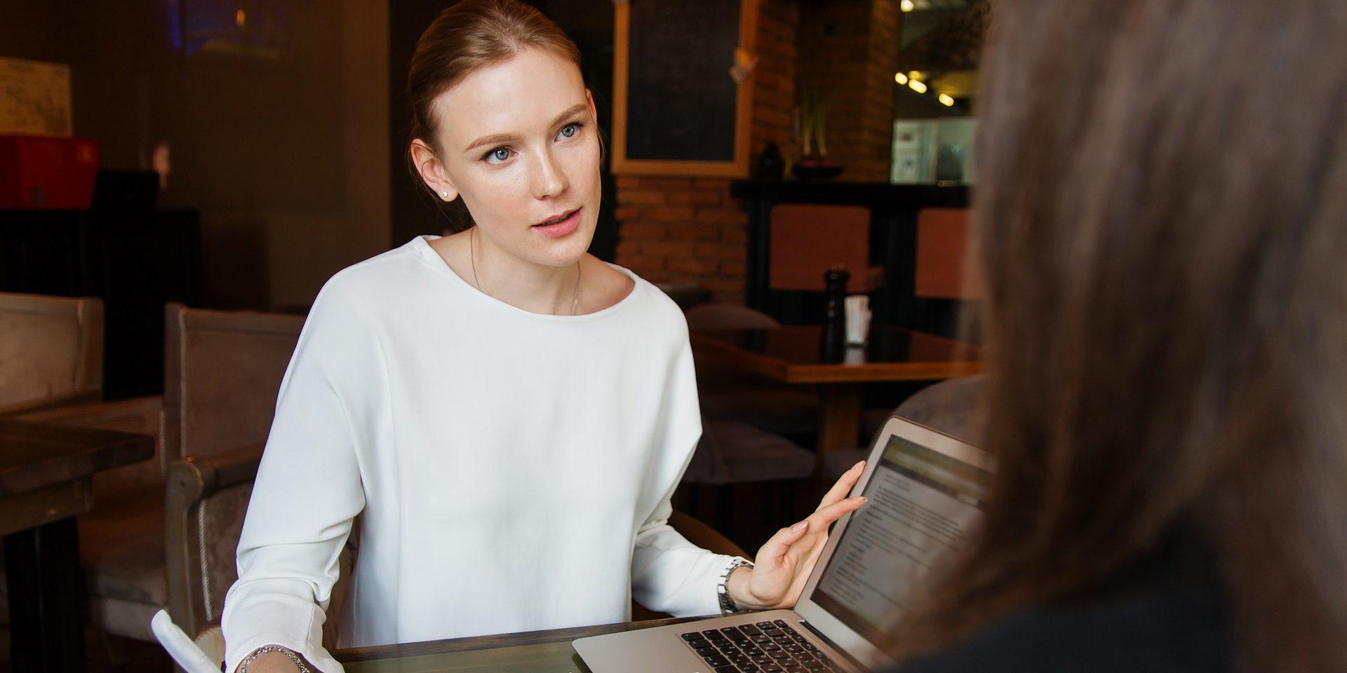 Eine Frau hört einer nicht eindeutig erkennbaren weiteren Person zu und macht Notizen zum Gespräch.