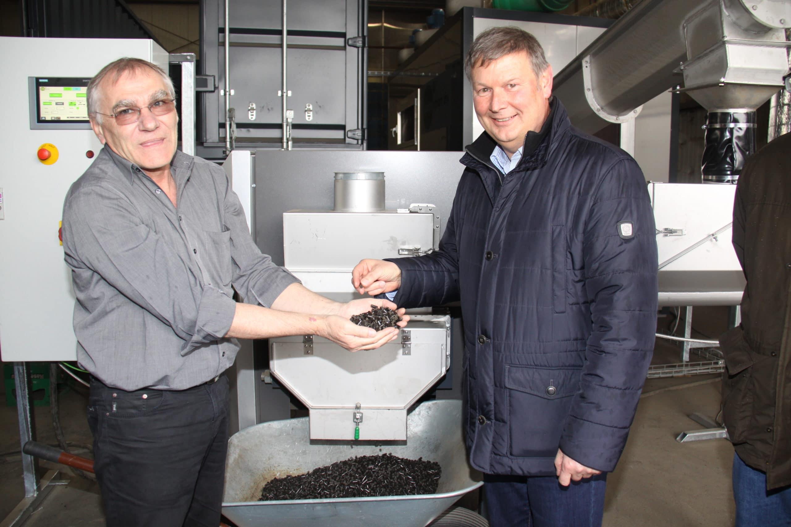 Firmenleiter Franz J. Kraus (links) präsentiert aus Klärschlamm gewonnene Pellets